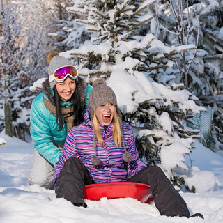 Two female friends on bobsleigh winter snow