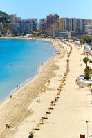 Sandy beach with parasols and vacationers, Penyal d'Ifac Natural Park view. Turquoise blue Sea water summer day. Seafront of Calpe spanish resort town. Costa Blanca, Alicante province, Spain
