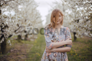 Girl in a flowering garden. Spring garden. Cheerful girl between trees with flowers. Cherry blossom