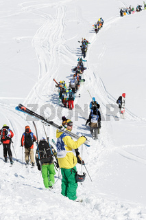 Skiers and snowboarders climb the mountain for freeride