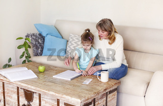 Grandmother teaching granddaughter to draw