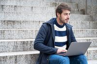 Handsome hipster modern businessman, using laptop in the city, with positive expression.