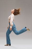 Energetic woman in stylish outfit jumping in studio