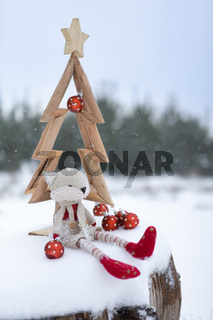 Simple Christmas tree in snow with baubles and christmas decorat