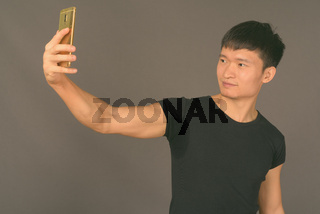 Studio shot of young Chinese man against gray background