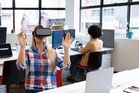Caucasian businesswoman sitting at desk using vr goggles in creative office