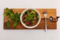 High angle view of bowl with salad and basil leaves on board on white background