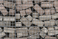 Stone wall of concrete bricks and mesh