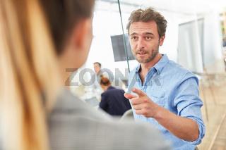 Business Mann diskutiert mit einer Kollegin