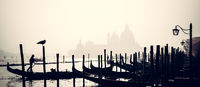 Romantic Italian city of Venice, a World Heritage Site: traditional Venetian wooden boats, gondolier and Roman Catholic church Basilica di Santa Maria della Salute in the misty background