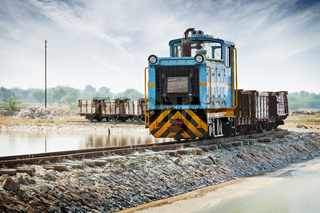 Old small blue locomotive and freight train