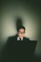 Portrait of handsome Persian businessman using laptop in dark room