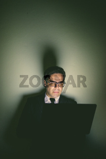 Portrait of handsome Persian businessman using laptop in dark room