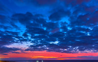 Colorful sky with clouds above the sea at twilight