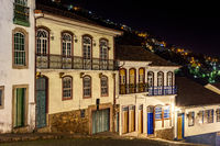 Facades of houses in colonial architecture on an old cobblestone street illuminated at night