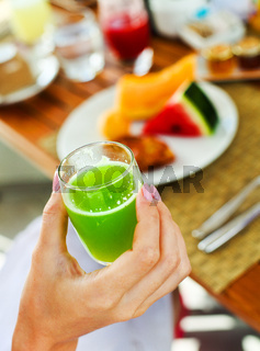 Woman holding glass of a green juice in her hand hand