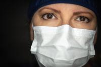 Female Doctor or Nurse Wearing Medical Face Mask on Dark Background