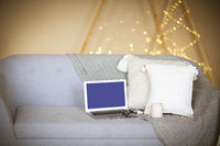 Laptop on sofa in room with festive lights