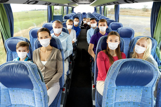 group of passengers in masks travelling by bus