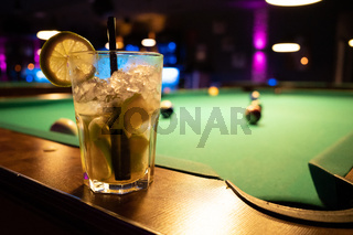 in a billiard parlor on the board of a billiard table is a glass with a cocktail
