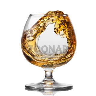 Splash of cognac in glass isolated