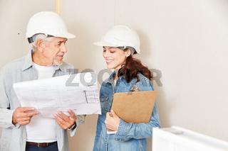 Architekten mit Bauplan und Checkliste