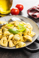 Tortellini pasta. Italian stuffed pasta with basil leaves.