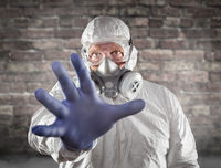 Man Wearing Hazmat Suit, Protective Gas Mask and Goggles Reaching Out With Hand