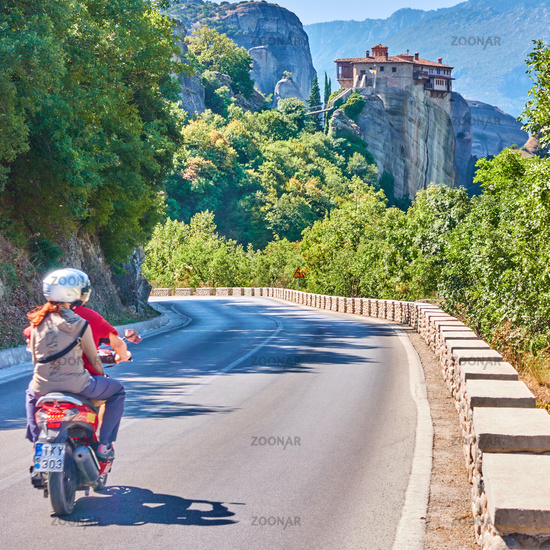 Motor scooter with tourists in Meteora