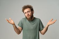 Handsome man with curly hair showing I don't know gesture with both hands isolated on white background. Portrait of confused young man on white background