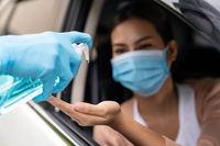 Medical staff give hand sanitiser at drive thru hospital