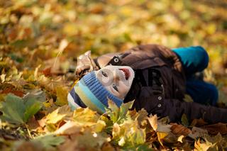 Portrait of a cheerful little boy wallow in fall foliage