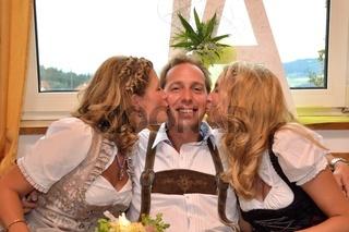 Frauen in Tracht kuessen Mann