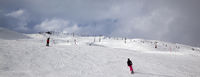 Snowy ski slope with skiers in high mountains and cloudy sunlit sky at winter day