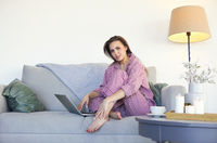 Relaxed female with hot drink watching movie on laptop
