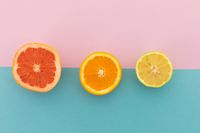 Grapefruit, orange and lemon halves on pink and blue background