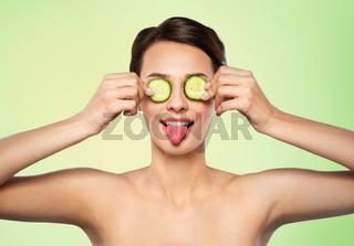 beautiful woman making eye mask of cucumbers