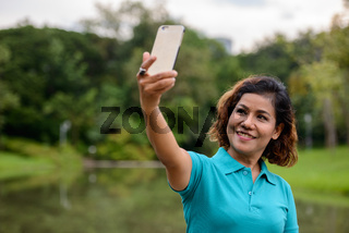 Happy mature beautiful Asian woman taking selfie at the park