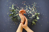 Female hands with manicure over table with plants and confetti