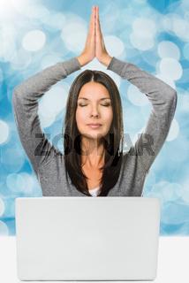 Hübsche Frau meditiert vor Laptop Computer