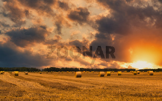 Sunset over a field of newly harvested hay