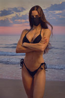 Sensual young lady pretty girl wear black color cloth mask and bikini pose on nature at sunrise near sea. Concept covid-19 outbreak. Obligatory compulsory use face masks outdoors. Fashion and beauty