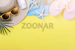 Beach accessories on the yellow background