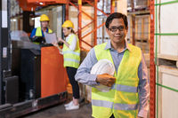 Portrait of asian warehouse manager with warehouse worker in background