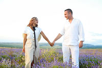 Cute young happy couple in love in a field of lavender flowers. Enjoy a moment of happiness and love in a lavender field