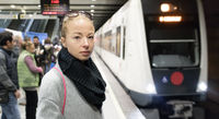 Young woman in winter coat going to work, waiting on the platform of a railway station for train to arrive. Public transport