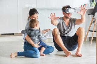 Mutter und Sohn beobachten Vater mit VR-Brille