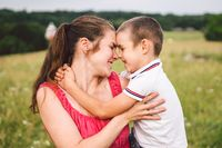 Woman spends time with a child in nature. Mother and son embracing in the park. Happy mom playing with her boy in the field on a glade. Having fun mama and toddler outdoor on summer day