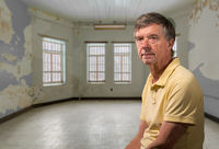 Senior caucasian man sitting in an empty and damaged room