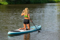 Caucasian woman paddles with SUP on water